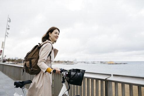 Smiling woman with e-bike having a break on beach promenade - JRFF02939