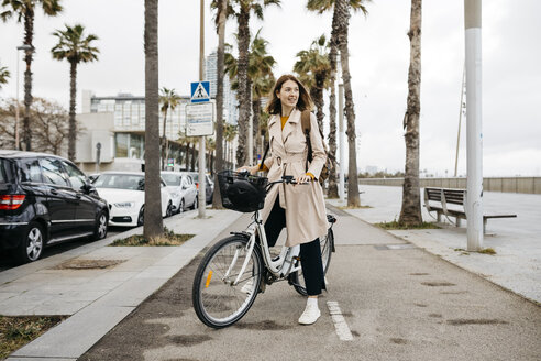 Smiling woman with e-bike on a promenade - JRFF02945