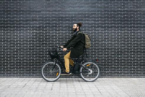 Man riding e-bike along a brick wall - JRFF02954