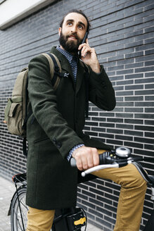 Man with e-bike talking on cell phone at a brick wall - JRFF02957