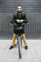 Portrait of smiling man with e-bike at a brick wall - JRFF02960