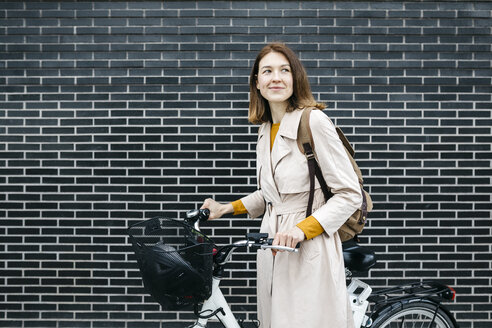 Smiling woman with e-bike at a brick wall - JRFF02963