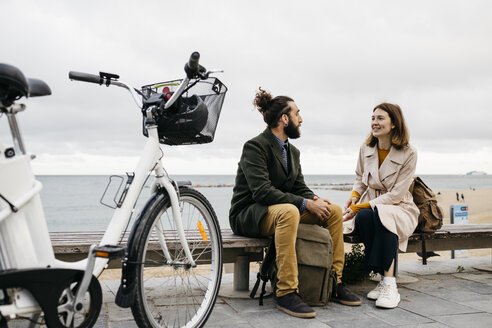 Couple sitting on a bench at beach promenade next to e-bike talking - JRFF02966