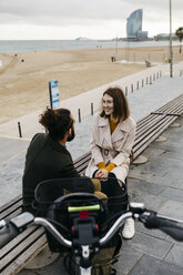 Couple sitting on a bench at beach promenade next to e-bike talking - JRFF02969