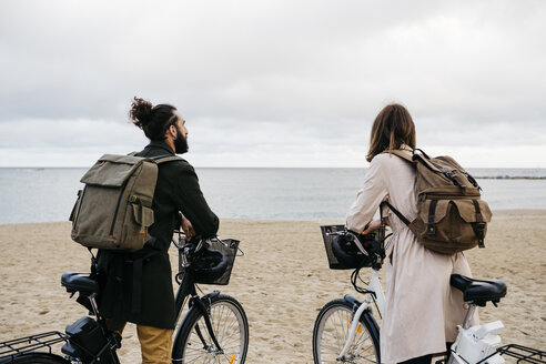 Couple with e-bikes on the beach looking at the sea - JRFF02972