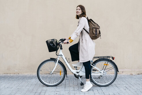 Woman with e-bike at a wall - JRFF02975