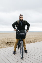 Portrait of happy man with e-bike at the beach - JRFF02978