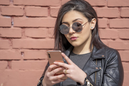Portrait of young woman wearing sunglasses and black leather jacket looking at smartphone - OCMF00375