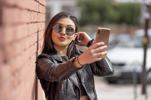 Portrait of young woman wearing sunglasses and black leather jacket taking selfie with smartphone - OCMF00378