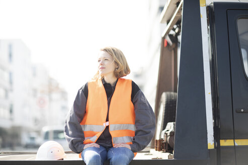 Woman wearing reflective vest sitting on truck platform - SGF02355