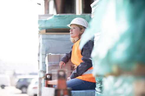 Woman wearing reflective vest and hard hat sitting on building material - SGF02358