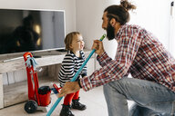 Father and little daughter having fun together while cleaning the living room - JRFF02986