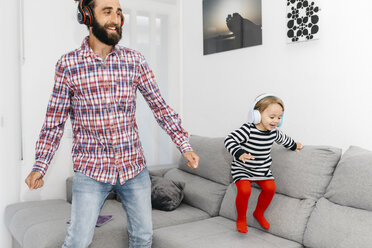 Father and little daughter dancing in the living room while listening music with headphones - JRFF02989