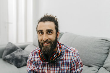 Portrait of bearded man with headphones at home - JRFF02992