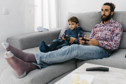 Portrait of father and son sitting together on the couch playing computer game - JRFF03004