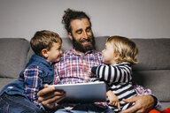 Happy father sitting on the couch with his children using digital tablet - JRFF03016