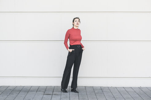 Elegant young woman standing at a wall - UUF17030