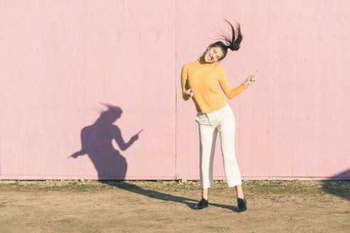 Happy young woman dancing in front of a pink wall - UUF17072