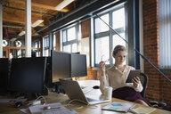 Businesswoman using digital tablet at office desk - HEROF34906