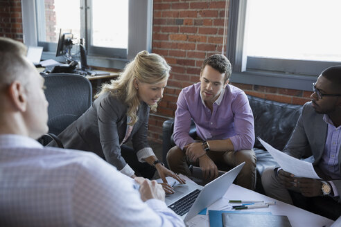 Business people working at laptop in meeting - HEROF34978