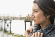Close up pensive brunette woman looking away lake - HEROF34990