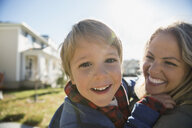 Close up portrait smiling mother holding sun outdoors - HEROF34993