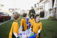 Coach and boys sports team gathering recycling neighborhood - HEROF34996