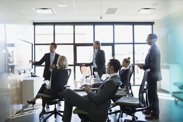 Businessman leading meeting at screen in conference room - HEROF35029