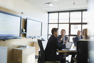 Businessman at laptop leading meeting in conference room - HEROF35032