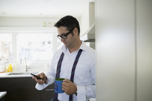Businessman drinking coffee using cell phone in kitchen - HEROF35077