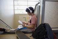 High school student headphones using digital tablet stairs - HEROF35140