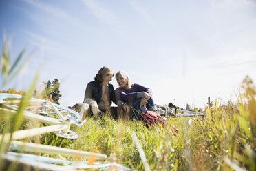 Friends smiling and resting near bicycles in sunny field - HEROF35281
