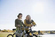 Grandmother and granddaughter with bicycles in sunny field - HEROF35287