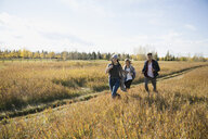 Friends running in sunny autumn field - HEROF35293