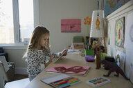 Girl using digital tablet at bedroom desk - HEROF35305