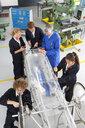 Teacher helping students constructing electric vehicle prototype in vocational school - JUIF00841