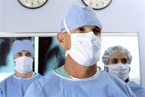 Close up portrait of serious surgeons in scrubs and surgical masks in front of x-rays - JUIF00847