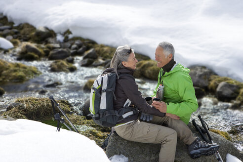 Smiling couple with backpack sitting on rock and drinking coffee near stream in snow - JUIF00850