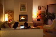 Couple using digital tablet on living room sofa facing fireplace - HOXF04341