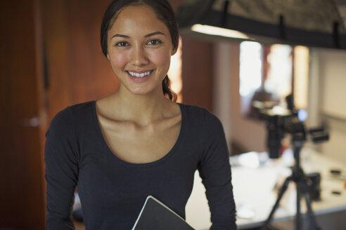 Portrait smiling, confident female photographer in studio - HOXF04350