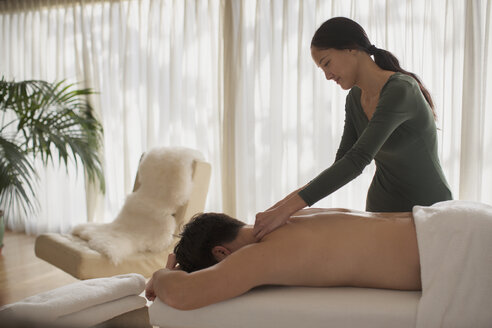 Female masseuse giving man massage - HOXF04377