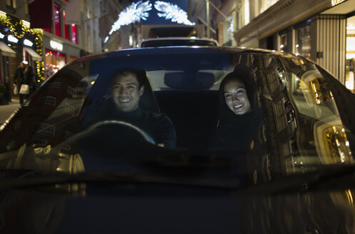 Smiling couple driving car at night - HOXF04380