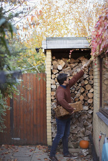Man reaching for firewood on autumn patio - HOXF04395