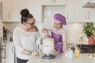 Mother and daughter decorating cake in kitchen - CAIF23064