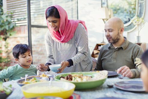Mother in hijab serving dinner to family at table - CAIF23109