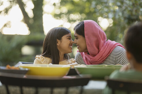 Affectionate mother in hijab rubbing noses at dinner table - CAIF23130