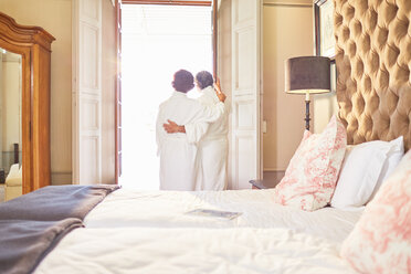 Couple in spa bathrobes standing at hotel balcony doorway - CAIF23169
