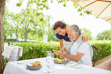 Mature couple dining, using smart phone at patio table - CAIF23172
