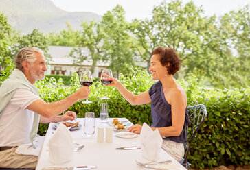Mature couple toasting wine glasses at patio restaurant table - CAIF23175