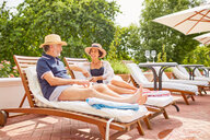 Mature couple relaxing on lounge chairs at sunny poolside - CAIF23178